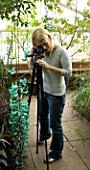 BLOND HAIRED GIRL WITH 35MM SLR DIGITAL CAMERA ON A TRIPOD IN A GREENHOUSE TAKING PHOTOGRAPHS OF A JADE VINE