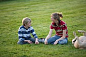 GIRL (AGED 15) AND BOY (AGED 12) SITTING IN A GARDEN AND LAUGHING  WITH DOG. FUN  ENJOYING  ENJOYMENT