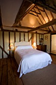 BOONSHILL FARM  EAST SUSSEX. INTERIOR OF BEDROOM WITH WOODEN FLOORBOARDS  EXPOSED BEAMS AND LINEN COVERED ARMCHAIRS AND MIRROR MADE FROM OLD WINDOW. DESIGNER: LISETTE PLEASANCE