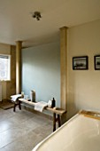 BOONSHILL FARM  EAST SUSSEX. INTERIOR OF BATHROOM WITH BATH AND WOODEN BENCH WITH MOTHER OF PEARL INLAY FROM INDIA. FRAMED PHOTOGRAPHS BY MICK SHAW. DESIGNER: LISETTE PLEASANCE