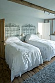 BOONSHILL FARM  EAST SUSSEX. INTERIOR OF GUEST BEDROOM WITH ANTIQUE LACE BEDSPREADS AND METAL GATES AS BEDHEADS. DESIGNER: LISETTE PLEASANCE
