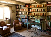 BOONSHILL FARM  EAST SUSSEX. INTERIOR OF STUDY WITH BOOKSHELVES MADE FROM RECLAIMED JOISTS MADE BY MICK SHAW. OLD LEATHER ARMCHAIRS AND OLD WOODEN DESK & CHAIR D: LISETTE PLEASANCE