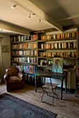BOONSHILL FARM  EAST SUSSEX. INTERIOR OF STUDY WITH BOOKSHELVES MADE FROM RECLAIMED JOISTS MADE BY MICK SHAW. OLD LEATHER ARMCHAIR AND OLD WOODEN DESK & CHAIR D: LISETTE PLEASANCE