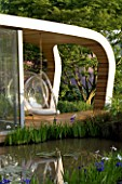 CHELSEA FLOWER SHOW 2007: GARDEN DESIGNED BY DIARMUID GAVIN. THE WESTLAND GARDEN. PAVILLION CLAD IN RED CEDAR WOOD WITH BUBBLE CHAIR AND RECYCLED TIMBER DECKING OVERLOOKING POND