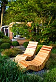 CHELSEA FLOWER SHOW 2007: GARDEN DESIGNED BY DIARMUID GAVIN. WESTLAND GARDEN. RECYCLED TIMBER CHAIRS OVERLOOK LUSH PLANTED GARDEN WITH RED CEDAR PAVILLION IN BACKGROUND