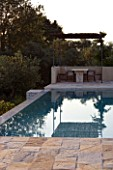CORFU  GREECE: VILLA ZOGRAFIA  NORTH EAST CORFU. DESIGN BY ALITHEA JOHNS OF SKOPOS DESIGN AND RAHDY ELWAN. SWIMMING POOL WITH COVERED DINING AREA IN EARLY MORNING