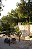 CORFU  GREECE: VILLA ZOGRAFIA  NORTH EAST CORFU. DESIGN BY ALITHEA JOHNS OF SKOPOS DESIGN AND RAHDY ELWAN. COURTYARD WITH ROCKS AND TREES  STONE WALL AND OLIVE TREES