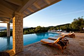 CORFU  GREECE: VILLA IN NORTH EAST CORFU. DESIGN BY ALITHEA JOHNS OF SKOPOS DESIGN AND RAHDY ELWAN. RECTANGULAR INFINITY SWIMMING POOL WITH SUN LOUNGERS AND COVERED CANOPY