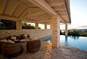 CORFU  GREECE: VILLA IN NORTH EAST CORFU. DESIGN BY ALITHEA JOHNS OF SKOPOS DESIGN AND RAHDY ELWAN. RECTANGULAR INFINITY SWIMMING POOL AT DAWN WITH WICKER SEATS AND COVERED CANOPY