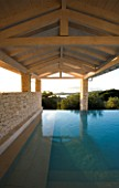 CORFU  GREECE: VILLA IN NORTH EAST CORFU. DESIGN BY ALITHEA JOHNS OF SKOPOS DESIGN AND RAHDY ELWAN. RECTANGULAR INFINITY SWIMMING POOL AT DAWN WITH COVERED CANOPY
