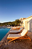 CORFU  GREECE: VILLA IN NORTH EAST CORFU. DESIGN BY ALITHEA JOHNS OF SKOPOS DESIGN AND RAHDY ELWAN. RECTANGULAR INFINITY SWIMMING POOL AT DAWN WITH SUN LOUNGERS