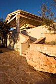 CORFU  GREECE: VILLA IN NORTH EAST CORFU. DESIGN BY ALITHEA JOHNS OF SKOPOS DESIGN AND RAHDY ELWAN. PATIO AND LARGE ROCK IN FRONT OF STEPS AND HOUSE