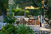 CORFU  GREECE. MALAMA HOUSE NEAR BARBATI. PATIO DINING AREA WITH PERGOLA  TABLE AND CHAIRS SET FOR ALFRESCO DINING. EVENING LIGHT  ROMANTIC  AMBIENCE  RELAXING  RELAXED