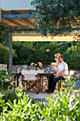 CORFU  GREECE. MALAMA HOUSE NEAR BARBATI. MAN (AGED 35) DRINKING A GLASS OF WINE AT A TABLE SET FOR ALFRESCO DINING BENEATH PERGOLA. PATIO  TABLE AND CHAIRS. RELAXED