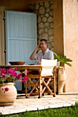 CORFU  GREECE. MAN (AGED 35) TALKING ON A MOBILE PHONE AT A TABLE. PATIO  TABLE AND CHAIRS. RELAXED  BUSINESS  SITTI NG