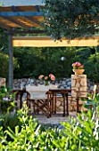 CORFU  GREECE. MALAMA HOUSE NEAR BARBATI. PATIO DINING AREA WITH TABLE AND CHAIRS SET FOR ALFRESCO DINING. EVENING LIGHT  ROMANTIC  AMBIENCE  RELAXING  RELAXED
