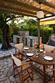 CORFU  GREECE. MALAMA HOUSE NEAR BARBATI. PATIO DINING AREA WITH TABLE AND CHAIRS AND BARBEQUE SET FOR ALFRESCO DINING. EVENING LIGHT  ROMANTIC  AMBIENCE  RELAXING  RELAXED