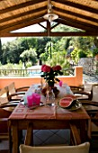 VILLA CHRISTINA   KAMINAKI  CORFU  GREECE: COVERED OUTDOOR PATIO/ TERRACE DINING AREA WITH WOODEN TABLE AND CHAIRS SET FOR ALFRESCO DINING