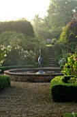 MARINERS GARDEN  BERKSHIRE. DESIGNER FENJA ANDERSON - THE ROSE GARDEN AT DAWN - ROSE PROSPERITY  ROSE COMPTE DE CHAMBORD  ROSA SANCTA AND BOX EDGING WITH FOUNTAIN IN THE CENTRE