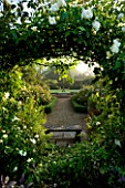 MARINERS GARDEN  BERKSHIRE. DESIGNER FENJA ANDERSON - VIEW INTO THE ROSE GARDEN THROUGH AN ARCH (MOON GATE) OF ROSE CITY OF YORK TO THE WATER LILY POOL WITH HERON SCULPTURE.