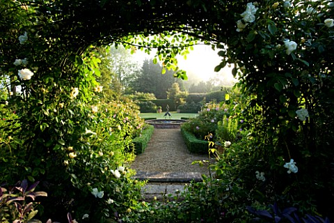 MARINERS_GARDEN__BERKSHIRE_DESIGNER_FENJA_ANDERSON__VIEW_INTO_THE_ROSE_GARDEN_THROUGH_AN_ARCH_MOON_G
