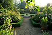 MARINERS GARDEN  BERKSHIRE. DESIGNER FENJA ANDERSON - VIEW INTO THE ROSE GARDEN TO THE WATER LILY POOL WITH HERON SCULPTURE. ROSES FANTIN LATOUR  FELICIA AND PROSPERITY