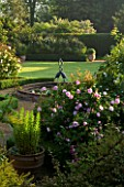 MARINERS GARDEN  BERKSHIRE. DESIGNER FENJA ANDERSON - VIEW INTO THE ROSE GARDEN TO THE WATER LILY POOL WITH HERON SCULPTURE. ROSES FANTIN LATOUR AND PROSPERITY