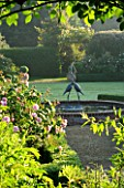 MARINERS GARDEN  BERKSHIRE. DESIGNER FENJA ANDERSON - VIEW INTO THE ROSE GARDEN TO THE WATER LILY POOL WITH HERON SCULPTURE. ROSE FANTIN LATOUR IN THE FOREGROUND