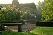 MARINERS GARDEN  BERKSHIRE. DESIGNER FENJA ANDERSON - VIEW INTO THE ROSE GARDEN AT DAWN TO THE WATER LILY POOL WITH HERON SCULPTURE.