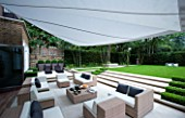 CONTEMPORARY TOWN/CITY/URBAN GARDEN DESIGNED BY CHARLOTTE SANDERSON: ENTERTAINING/RELAXING AREA WITH AWNING  TABLE  CHAIRS  SOFAS WITH STEPS LEADING TO LAWN
