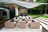 CONTEMPORARY TOWN/CITY/URBAN GARDEN DESIGNED BY CHARLOTTE SANDERSON: AWNING OVER ENTERTAINING/RELAXING AREA WITH TABLE  CHAIRS AND SOFAS AND STEPS LEADING TO LAWN