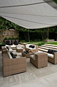 CONTEMPORARY TOWN/CITY/URBAN GARDEN DESIGNED BY CHARLOTTE SANDERSON: AWNING OVER ENTERTAINING/DINING AREA WITH TABLE/CHAIRS/SOFAS AND STEPS LEADIN TO LAWN