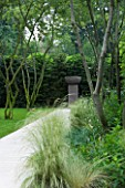 CONTEMPORARY TOWN/CITY/URBAN GARDEN DESIGNED BY CHARLOTTE SANDERSON: BORDER WITH GRASSES AND LIMESTONE PATH LEADING TO URN ON PLINTH. FOCAL POINT