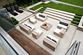 URBAN CONTEMPORARY MODERN MINIMALIST GARDEN DESIGNED BY CHARLOTTE SANDERSON: VIEW FROM ROOF ONTO PAVED PATIO AREA WITH TABLE AND CHAIRS  STEPS UP TO LAWN