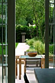 URBAN CONTEMPORARY MODERN MINIMALIST GARDEN DESIGNED BY CHARLOTTE SANDERSON: VIEW THROUGH KITCHEN DOOR TO PATIO WITH WOODEN TABLE AND CHAIRS AND PAVED PATH TO URN