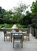 URBAN CONTEMPORARY MODERN MINIMALIST GARDEN DESIGNED BY CHARLOTTE SANDERSON: STONE PATIO WITH WOODEN TABLE AND CHAIRS AND PAVED PATH TO URN  LAWN