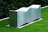 URBAN CONTEMPORARY MODERN MINIMALIST GARDEN DESIGNED BY CHARLOTTE SANDERSON: A PLACE TO SIT - METAL WAVE SEAT/ BENCH ON LAWN/ GRASS BESIDE YEW HEDGE