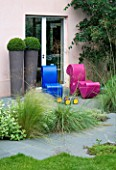 GARDEN DESIGNED BY CHARLOTTE SANDERSON: GREY SLATE PATH LEADS TO PATIO WITH PINK AND BLUE MODERN CHAIRS AND TWO TALL CYCLINDRICAL CONTAINERS PLANTED WITH BOX