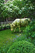 GARDEN DESIGNED BY CHARLOTTE SANDERSON: MODEL COW IN THE LAWN WITH CORNUS KOUSA BEHIND IN SPRING