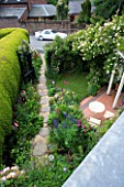 AMELIA HEATH GARDEN: 1 CROSS VILLAS SHROPSHIRE: PATIO: TABLE AND CHAIRS. WOODEN WITH ROSE GOLDFINCH  GLADIOLUS BYZANTINUS  GRAVEL PATH  CLEMATIS ETOILE VIOLETTE  ACONITUM