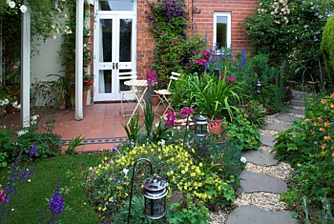 AMELIA_HEATH_GARDEN__1__CROSS_VILLAS__SHROPSHIRE_PATIO_BESIDE_THE_HOUSE__WOODEN_TABLE_AND_CHAIRS__PE