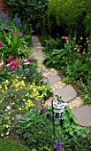 AMELIA HEATH GARDEN  1  CROSS VILLAS  SHROPSHIRE: PATIO BESIDE THE HOUSE - LANTERN  GLADIOLUS COMMUNIS BYZANTINUS  ACONITUM  GRAVEL PATH WITH STEPPING STONES