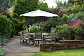 MARINERS GARDEN  BERKSHIRE. DESIGNER FENJA ANDERSON - PATIO WITH WINE AND RED BORDER AND UPPER BANK -  A PLACE TO SIT - TABLE AND CHAIRS AND CANOPY - PHYGELIUS  PENSTEMON FIREBIRD