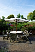 MARINERS GARDEN  BERKSHIRE  DESIGNER FENJA ANDERSON - TABLE  CHAIRS AND CANOPY ON THE PATIO BESIDE THE KITCHEN