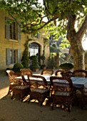 DESIGNER DOMINIQUE LAFOURCADE  PROVENCE  FRANCE - LARGE GRAVEL TERRACE WITH PROVENCAL FARMHOUSE  WICKER CHAIRS  TABLE