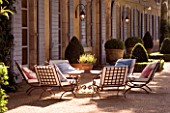 DESIGNER DOMINIQUE LAFOURCADE  PROVENCE  FRANCE - PROVENCAL FARMHOUSE WITH BLUE SHUTTERS  GRAVEL TERRACE WITH METAL TABLE AND CHAIRS WITH CUSHIONS. A PLACE TO SIT. EVENING LIGHT