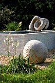 PROVENCE  FRANCE. GARDEN OF MARCO NUCERA. GRAVEL GARDEN WITH BEAUTIFUL WOODEN SCULPTURED BALL  YUCCA  WATER FEATURE AND TWISTED SCULPTURE