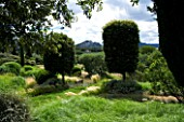 DESIGNER ALAIN DAVID IDOUX - MAS BENOIT  PROVENCE  FRANCE. VIEW TO MOUNTAINS WITH GRASS PATH AND STIPA TENUISSIMA