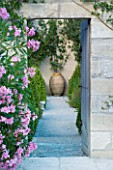 DESIGNER MICHEL SEMINI  PROVENCE  FRANCE. VIEW THROUGH DOORWAY PAST PINK OLEANDER ALONG PATH TO TERRACOTTA CONTAINER. FOCAL POINT