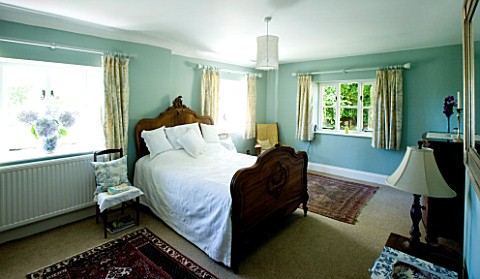 DESIGNER_CLARE_MATTHEWS__DEVON_BLUE_AND_WHITE_THEMED_BEDROOM_WITH_WOODEN_BED_AND_BLUE_HYDRANGEA_FLOW